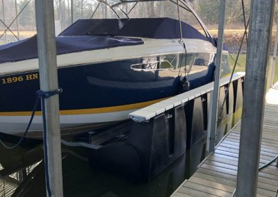 A blue and white cabin boat on a HarborHoist boat lift next to an aluminum boat dock with a roof