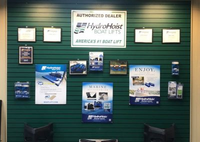 Green showroom wall with HydroHoist boat lifts signs and information and sample materials on and in front of it