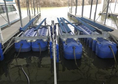 A blue HydroHoist Ultralift boat lift sitting empty in the water surrounded by a dock on both sides