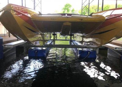 A close up view of the front of a yellow and red boat sitting out of the water on top of a blue HydroHoist Ultralift next to a dock