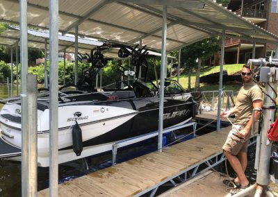 A white and black ski boat sitting on top of a blue HydroHoist Ultralift boat lift next to a dock with a man standing on it