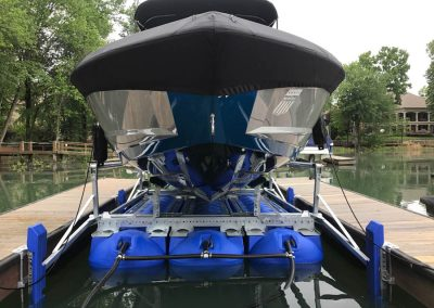 The front view of a white and blue boat with a black cover on it sitting out of the water on a blue HydroHoist Ultralift boat lift