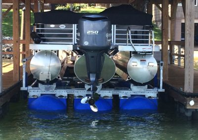 A black pontoon boat sitting out of the water on top of a blue HydroHoist Ultralift boat lift surrounded by a wood dock