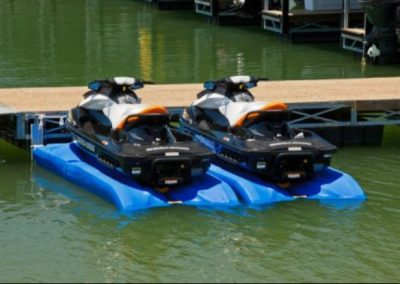 Two hydroport jetski lifts next to each other with black, white, and orange jet skis on top of them in front of a dock