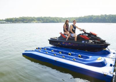 A young boy and girl sitting together on a red jetski next to a blue hyrdrohoist on a lake with trees in the background