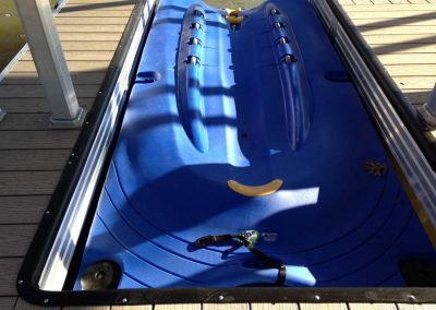 A close up shot of a blue hydroport jetski lift surrounded by an aluminum floating dock