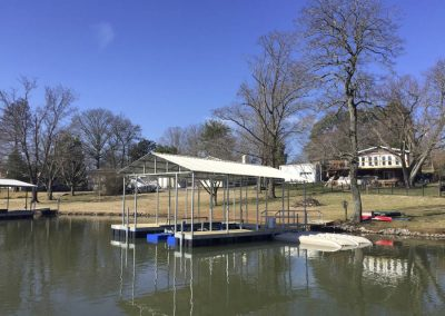 An aluminum floating boat dock with roof and hydroport on the shore of a river with houses in the background