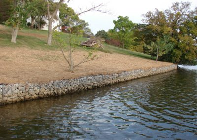 Rip Rap Erosion Control Rocks along curved shoreline with trees and white house in the background