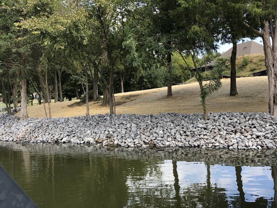 Rocks along a shoreline with a field and house in the background and river in the foreground