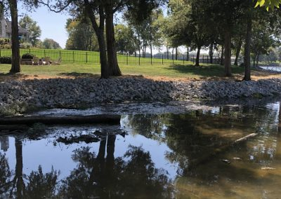 Rip rap erosion control rocks alone the shoreline of a river with trees in the background