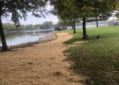 A path on the shore next to rip rap erosion control rocks along the shoreline of the river with large green trees lining the path