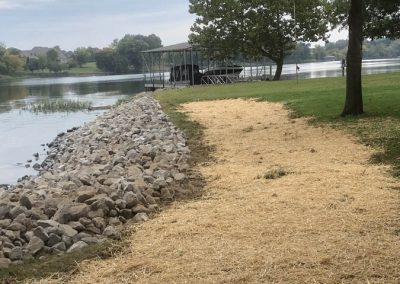 A path lined with trees along the rip rap erosion control rocks on the shoreline of the river leading to a floating boat dock