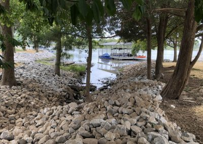 Rip rap erosion control rocks on a shoreline surrounded by trees with an aluminum floating boat dock in the background