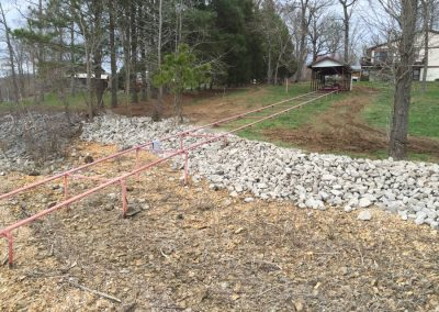 Rip rap erosion rocks on a dry riverbed in the backyard of large house with the framework of a dock being built
