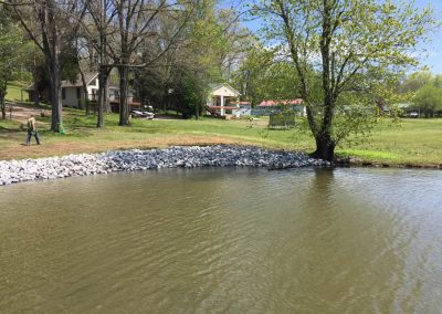A backyard of a house with rip rap erosion control rocks along the shoreline of a river