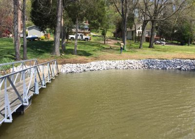 A gangway leading to a backyard of a house with rip rap erosion control rocks along the shoreline of a river