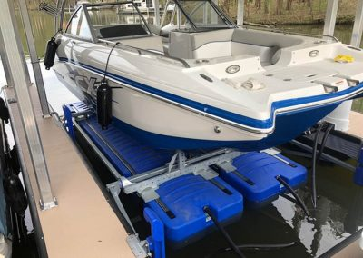 A white and blue boat sitting out of the water out of the water on a shallow water boat lift